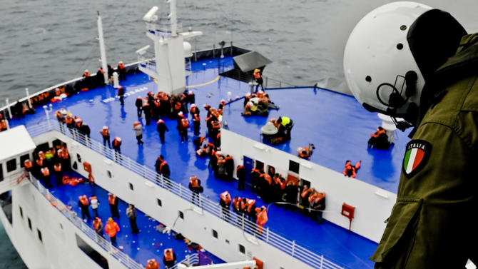 In this image released by the Italian Navy, passengers and crew are seen on the deck of the Italian-flagged ferry Norman Atlantic as it is approached by a rescue helicopter after it caught fire in the Adriatic Sea, Sunday, Dec. 28, 2014. Italian and Greek rescue crews battled gale-force winds and massive waves as they struggled Sunday to evacuate hundreds of people from a ferry on fire and adrift in the channel between Italy and Albania. At least one person died and two were injured. The fire broke out before dawn Sunday on a car deck of the Italian-flagged Norman Atlantic, traveling from the western Greek port of Patras to the Italian port of Ancona on the Adriatic, with 422 passengers and 56 crew members on board. (AP Photo/Italian Navy)