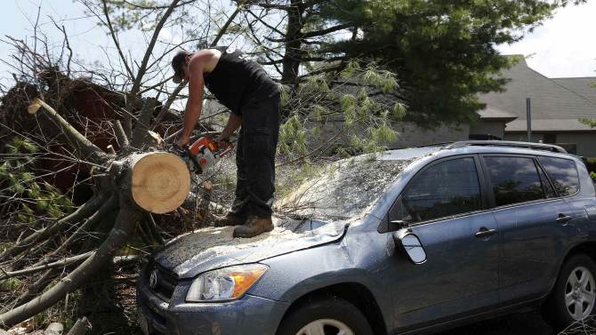 A worker cuts a tree from on top of a storm-damaged car on Beach Street in Revere, Massachusetts