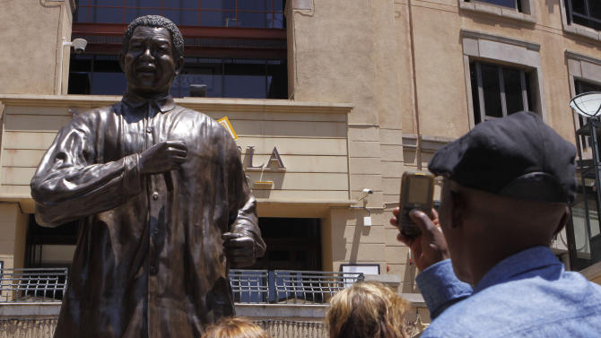 """People take photos of the giant statue of former president Nelson Mandela, in Mandela Square, Johannesburg, South Africa, Sunday Dec. 9, 2012. South Africans prayed Sunday for the health of former President Nelson Mandela and anxiously awaited further word about the anti-apartheid leader after he was admitted to a military hospital. President Jacob Zuma visited Mandela Sunday morning at the hospital in Pretoria and found the frail 94-year-old to be """"comfortable and in good care,"""" presidential spokesman Mac Maharaj said in a statement. Maharaj offered no other details about Mandela, nor what medical tests he had undergone since entering the hospital Saturday.  (AP Photo/Denis Farrell)"""