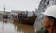 A rescue boat sails through a flooded street in Anju City, South Phyongan Province, North Korea, Monday, July 30, 2012. More heavy rain has pounded North Korea, flooding buildings and farmland and forcing stranded people and their livestock to take shelters atop rooftops. (AP Photo/Kim Kwang Hyon)