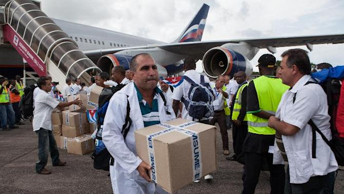 The first members of a team of 165 Cuban doctors and health workers unload boxes of medicine and medical material from a plane upon their arrival at Freetown's airport to help the fight against Ebola in Sierra Leone, on October 2, 2014
