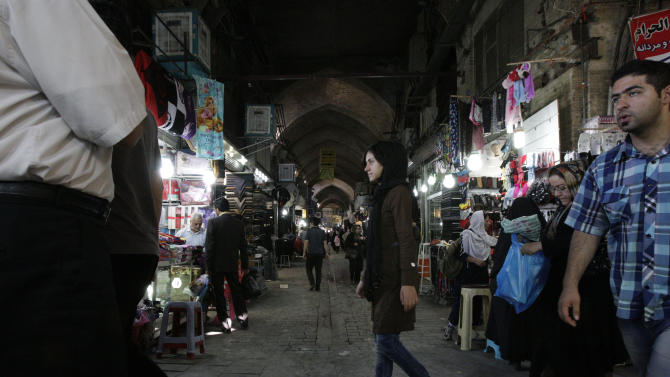 Iranians shop at Tehran's old main bazaar in downtown Tehran, Iran, Sunday, Oct. 7, 2012. Iran's parliament on Sunday abandoned its planned impeachment of a Cabinet minister over the free-fall of the country's currency, opting instead to look for more effective economic measures, like cutting spending. The aborted move to impeach the minister reflects unease over the severe drop in the value of the Iranian rial, mostly because of Western sanctions over Iran's suspect nuclear program. On Sunday the parliament approved outlines of a bill to restrict the government's use of different exchange rates for its foreign revenue and requiring the return of some funds to the treasury. (AP Photo/Vahid Salemi)