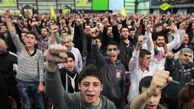 """Hezbollah supporters cheer as they listen to a speech by Hezbollah leader Hassan Nasrallah, during a ceremony to mark Islam's Prophet Muhammad's birth in the southern suburbs of Beirut, Lebanon, Friday, Jan. 25, 2013. Nasrallah, a staunch ally of the Syrian regime, said those who had dreamed about """"dramatic changes"""" taking place in Syria should let go of their dreams. He said all military, political and international indications showed that President Bashar Assad's regime cannot be defeated. (AP Photo/Bilal Hussein)"""