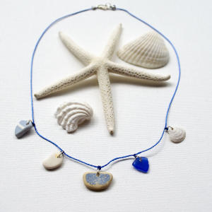 """This undated publicity photo provided by Karen Vesk shows a necklace that incorporates blue beach glass, a small shell and several shards of beach pottery. Vesk, of Erie, Penn., hunts for beach glass and pottery shards at the Lake Erie shoreline. She visits Southern states' beaches for small shells and shell fragments, which she says have """"an almost sculptural, abstract look to them."""" (AP Photo/Karen Vesk)"""