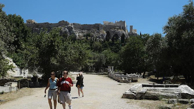 Visitors walk at the area of the 2nd century B.C, rebuilt ancient Stoa of Attalos, under the Acropolis hill in Athens, Friday, June 22, 2012. In Greek mythology, King Sisyphus pushed a boulder up a hill, over and over, forever, in a futile exercise that a few commentators have compared to international efforts to revive Greece's dire finances. Homer's Odyssey, whose protagonist endures years of peril on his way home after the Trojan War, is seen as another metaphor for the ordeal of a nation in its fifth year of recession. (AP Photo/Petros Karadjias)