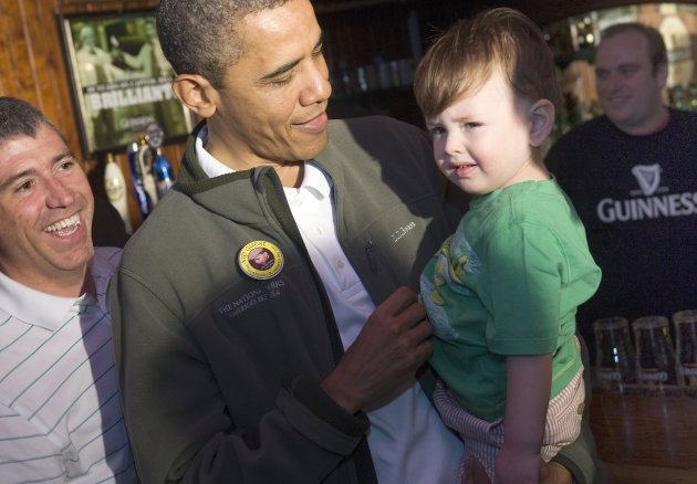 U.S. President Barack Obama (C) holds Cooper 'Danny' Coleman, 21-months-old, as he celebrates St. Patrick's Day with a stop at the Dubliner pub in Washington, March 17, 2012. REUTERS/Jonathan Ernst (UNITED STATES