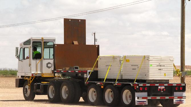 A truck carries the first two containers of low-level radioactive waste from Los Alamos National Laboratory in New Mexico, inside the grounds of a federal disposal site Thursday, June 6, 2013, near Andrews, Texas, as it begins a short trip down to where they were placed into a reinforced 8-inch-thick concrete container and will remain forever. Officials from the Dallas-based company, the Department of Energy, New Mexico and Texas cut the ribbon to open the site a short time before the two containers were placed in the more than 9-foot-deep container. (AP Photo/Betsy Blaney)