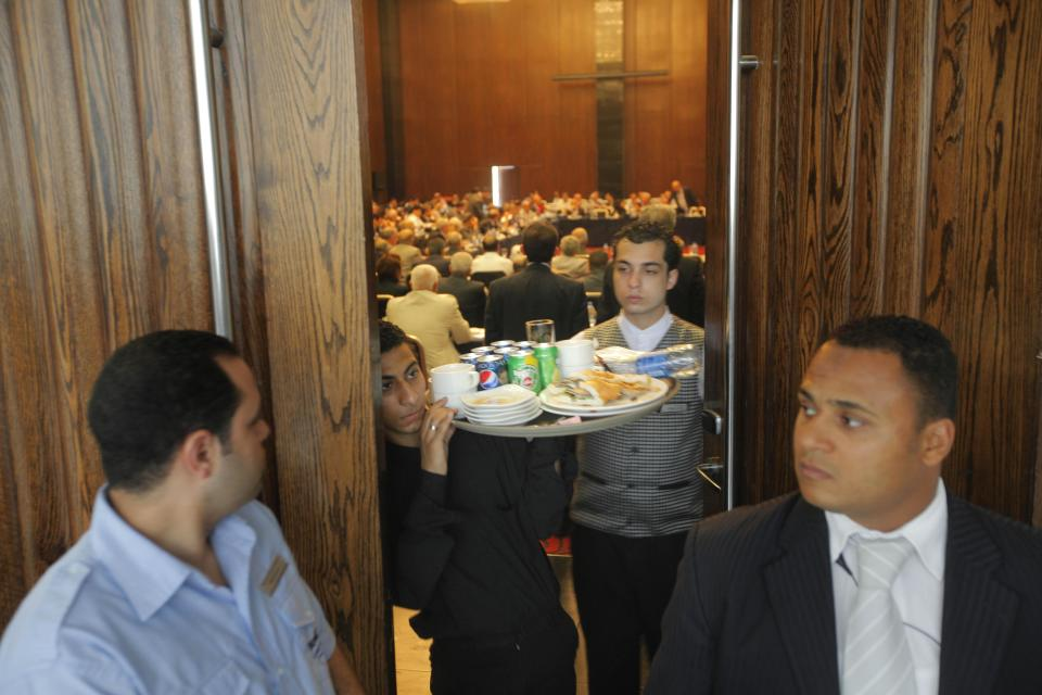 Egyptian security stands guard as a  waiter carries away a tray from a Syrian opposition meeting in New Cairo, Egypt, Tuesday, July 3, 2012. The Arab League chief urged exiled Syrian opposition figures to unite at a meeting as a new Western effort to force President Bashar Assad from power faltered. (AP Photo/Amr Nabil)
