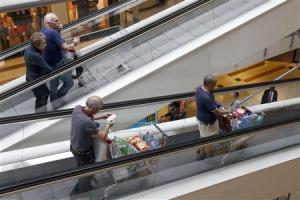 Customers push shopping trolleys on an escalator at the Bercy shopping centre in Charenton Le Pont, near Paris