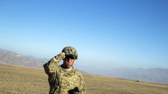 A U.S. soldier from Dragon Company of the 3rd Cavalry Regiment shields his eyes from the sun during a mortar exercise near forward operating base Gamberi in the Laghman