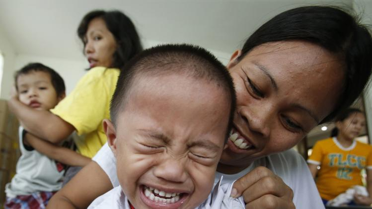 A boy cries after receiving a polio vaccination at a health centre in BASECO compound in Tondo, Manila