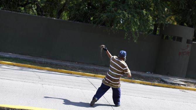 Man throws a stone at the 41st infantry battalion during a demonstration demanding justice for the 43 missing students from Ayotzinapa Teacher Training College in Iguala, Guerrero