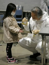 A girl holds out her hands for a radiation scan at a screening center in Koriyama in Fukushima prefecture on March 22, 2011. Tens of thousands of people were evacuated from an area around the Fukukshima plant to avoid radiation contamination. Many have still not been allowed home, with some areas expected to be uninhabitable for decades