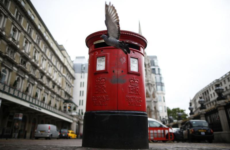 A pigeon flies past a Royal Mail post box outside Charing Cross station in central London