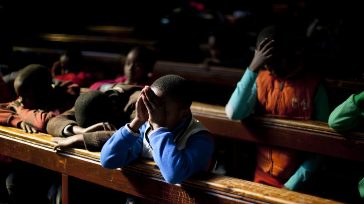 School children pray in the Regina Mundi church in Soweto township on the outskirt of  Johannesburg, South Africa, Sunday June 16, 2013.  Former South African president Nelson Mandela remained hospitalized for the ninth day with an occurring lung infection. (AP Photo/Jerome Delay)