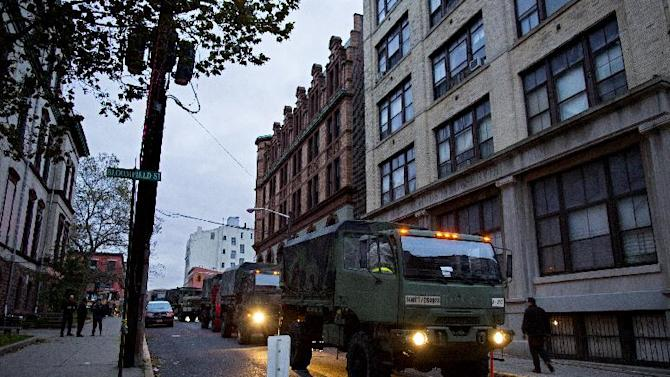 Members of the National Guard stand ready with large trucks used to pluck people from high water in Hoboken, N.J. Wednesday, Oct. 31, 2012 in the wake of superstorm Sandy. Parts of the city are still covered in standing water, trapping some residents in their homes. (AP Photo/Craig Ruttle)