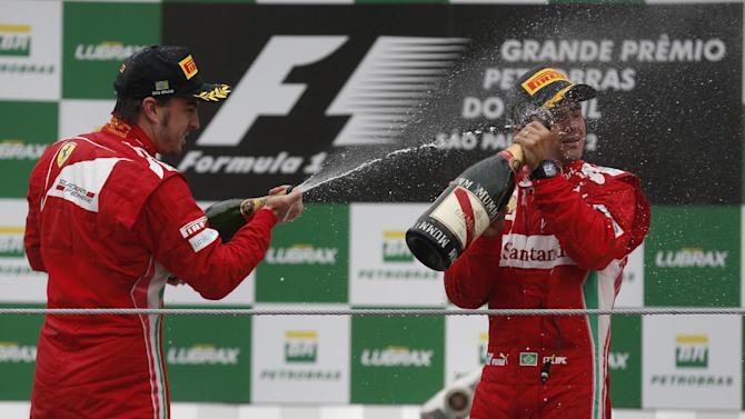 Ferrari driver Fernando Alonso of Spain, left, throws champagne to Ferrari driver Felipe Massa of Brazil during the Formula One Brazilian Grand Prix at Interlagos race track in Sao Paulo, Brazil, Sunday, Nov. 25, 2012. Red Bull driver Sebastian Vettel, of Germany, overcame a first-lap crash to clinch his third straight Formula One championship title on Sunday, finishing sixth in an incident-filled Brazilian Grand Prix won by Jenson Button under pouring rain.(AP Photo/Victor R. Caivano)