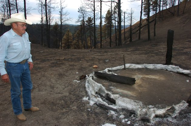 A July 20, 2012 photo shows Cecil Kolka examining the remains of a fiberglass water tank in the Custer National Forest that melted during the Ash Creek Fire near Volborg, Mont. Kolka's family lost an estimated 400 cows and calves to the 390-square-mile blaze.(AP Photos/Matthew Brown)
