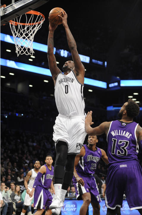 Brooklyn Nets' Andray Blatche (0) drives to the basket past Sacramento Kings' Travis Outlaw (25) and Derrick Williams (13) in the first half of an NBA basketball game on Sunday, March 9, 2014,