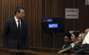 Parents of Reeva Steenkamp look on as South African Olympic and Paralympic sprinter Oscar Pistorius enters a court in Pretoria