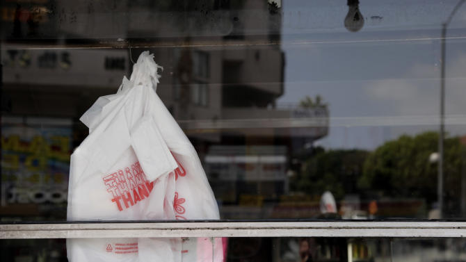 Plastic bags are seen through the window of a restaurant in Los Angeles, Thursday, May 24, 2012. Now that the city of Los Angeles has taken the first step toward banning plastic bags, it appears the little utilitarian bags themselves may be headed for the trash heap of history. (AP Photo/Jae C. Hong)