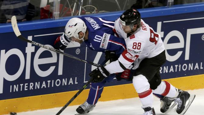 Switzerland's Romy fights for the puck with France's Meunier during their Ice Hockey World Championship game at the O2 arena in Prague