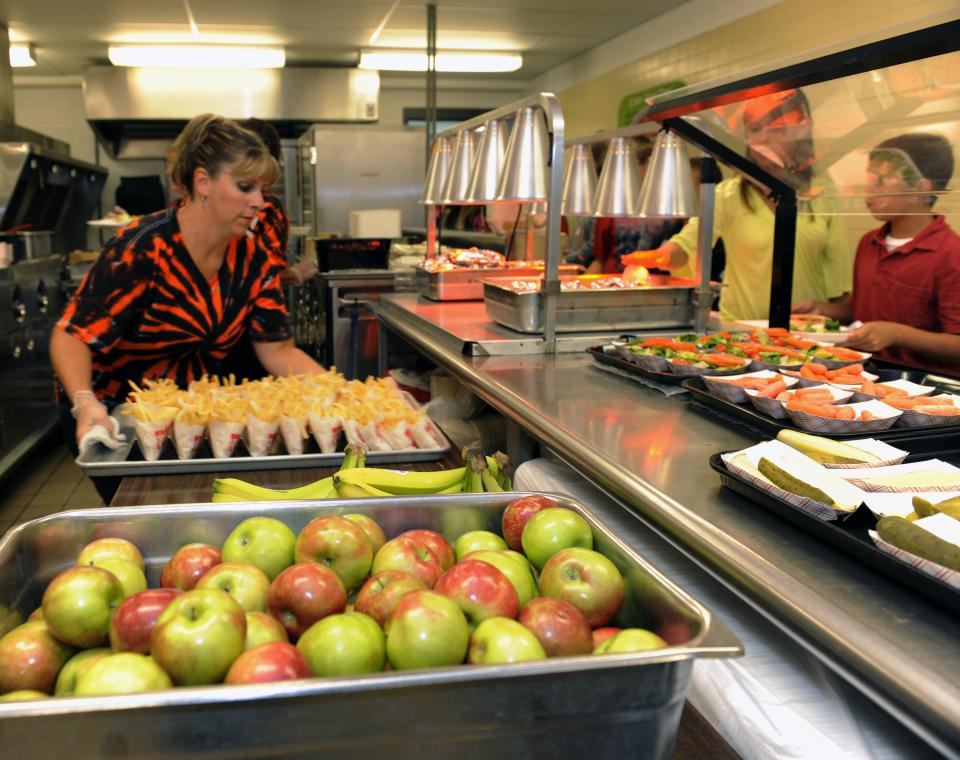 Michel Sasso, replenish's food items along the lunch line of the cafeteria at Draper Middle School in Rotterdam, N.Y., Tuesday, Sept. 11, 2012. The leaner, greener school lunches served under new federal standards are getting mixed grades from students. (AP Photo/Hans Pennink)