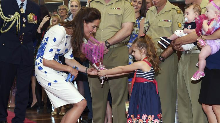 Catherine, Duchess of Cambridge, receives a bouquet from McCabe as she meets with families of service personnel at RAAF Base Amberley near Brisbane