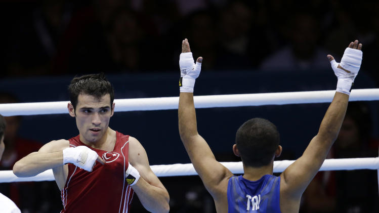 Turkey's Ferhat Pehlivan, left, reacts after defeating Trinidad & Tobago's Carlos Suarez in a light flyweight 49-kg preliminary boxing match at the 2012 Summer Olympics, Tuesday, July 31, 2012, in London. (AP Photo/Patrick Semansky)