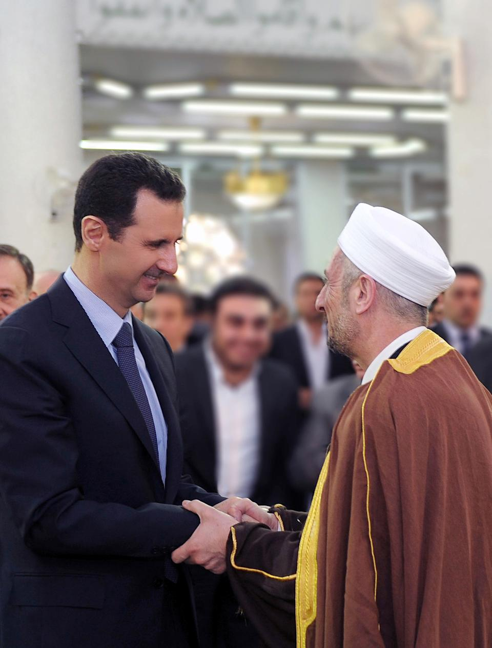In this photo released by the Syrian official news agency SANA, Syrian President Bashar Assad, left, shakes hands with a Syrian man, right, after prayers on the first day of Eid al-Adha at the Sayeda Hassiba mosque, in Damascus, Syria, Tuesday, Oct. 15, 2013. (AP Photo/SANA)
