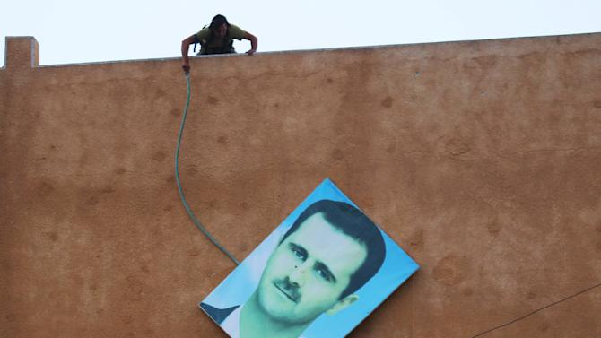 A member of al Qaeda's Nusra Front takes down a picture of Syria's President Bashar al-Assad in the northwestern city of Ariha, after a coalition of insurgent groups seized the area in Idlib province