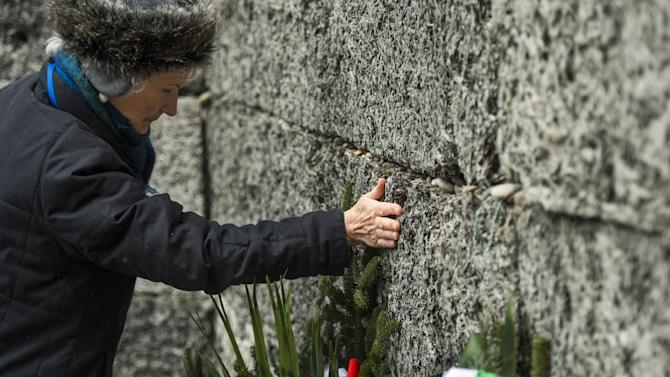 """A Holocaust survivor pays tribute to fallen comrades, putting her hand on the """"death wall"""" execution spot in the former Auschwitz concentration camp in Oswiecim, Poland, on January 27, 2015"""