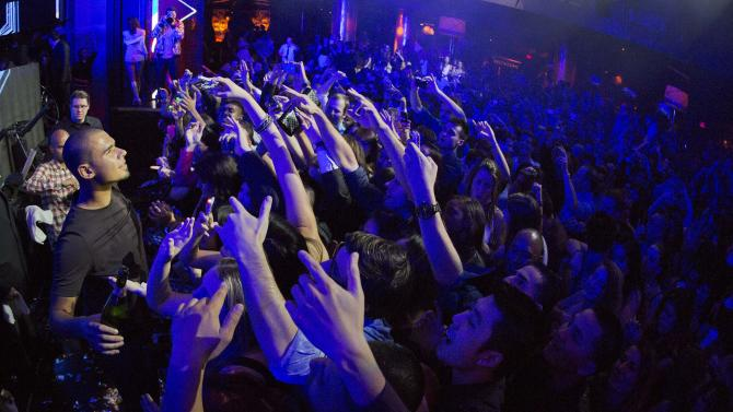 DJ Afrojack, left, holds a champagne bottle as he prepares to spray a crowd of revelers while performing at the XS nightclub in Las Vegas on Sunday, Jan. 20, 2013. (AP Photo/Julie Jacobson)