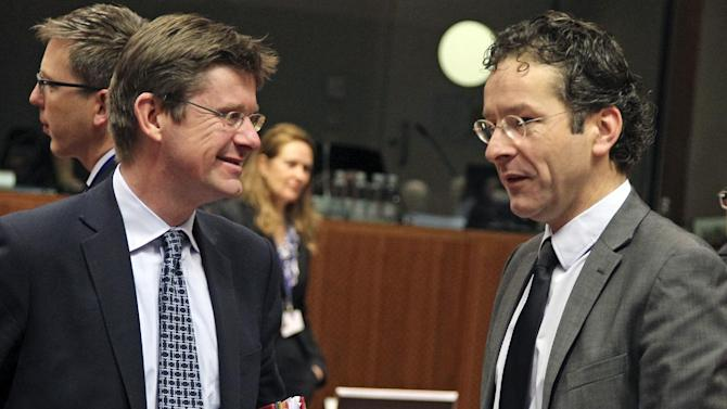 British Financial Secretary to the Treasury Greg Clark, left, talks with Dutch Finance Minister Jeroen Dijsselbloem, during the EU finance ministers meeting, at the European Council building in Brussels, Tuesday, Dec. 4, 2012. European Union finance ministers will seek to agree Tuesday to the principles of a eurozone banking supervisor, EU diplomats said. Earlier this year, the 27 member states pledged to reach the outlines of an agreement by the end of 2012, allowing the supervisor to come into force during the course of the following year. (AP Photo/Yves Logghe)