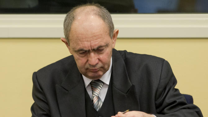 Zdravko Tolimir, a former high-ranking Bosnian Serb army officer charged with crimes including genocide in the 1995 Srebrenica massacre, takes pen and paper out of his suitcase as he waits for the the Yugoslav war crimes tribunal to deliver its judgment in The Hague, Wednesday Dec. 12, 2012. (AP Photo/Peter Dejong, Pool)