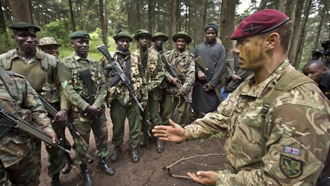 FILE - In this Thursday, Dec. 5, 2013 file photo, Corporal Andrew Smith of Britain's 3rd Battalion, The Parachute Regiment, right, instructs rangers of the Kenya Wildlife Service and Kenya Forest Service about the use of hand signals while patrolling, as they stage a demonstration of the skills they have learned over the last few days of joint anti-poaching training, in the forest near Nanyuki, Kenya. Africa is getting tougher in its fight against poaching with new laws with stiff penalties, more military training for rangers, and new technology like drones with thermal cameras are all helping to protect rhinos and elephants. (AP Photo/Ben Curtis, File)