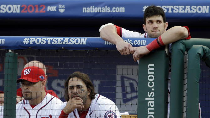 Washington Nationals' Bryce Harper, right, looks on from the dugout railing alongside teammates Henry Rodriguez, left, and Michael Morse during the eight inning of Game 3 of the National League division baseball series against the St. Louis Cardinals on Wednesday, Oct. 10, 2012, in Washington. St. Louis won 8-0. (AP Photo/Pablo Martinez Monsivais)