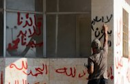 "A gunman who said he is a member of a Jihadist group called Shura Taliban Islam writes a slogan near graffiti reading ""Our leader is forever Mohammed"". After the Russian and Chinese veto of a UN resolution on Syria, America must use back channels to bolster its support for rebel forces as US military involvement is not an option, analysts said"