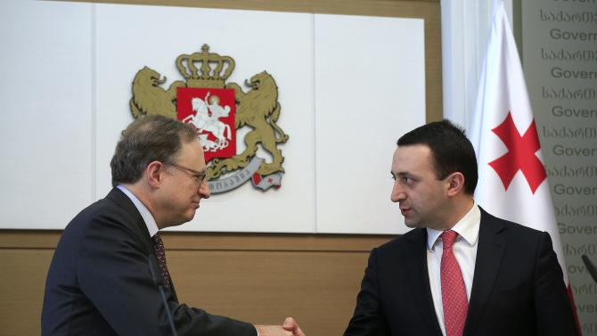 Georgia's PM Garibashvili and NATO Deputy Secretary General Vershbow shake hands after joint news conference in Tbilisi