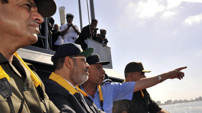 In this Sunday, Oct. 21, 2012, photo released by the Egyptian Presidency, Egyptian President Mohammed Morsi, second left, observes a military drill dubbed Naval Victory 45, from the frigate Toshka in the Mediterranean sea off the coast of Alexandria, Egypt. The drill involved dozens of naval vessels, Chinook helicopters and F-16 fighter jets in a commemoration of the 1967 sinking of the Israeli destroyer Eilat by Egypt. The Israeli military says its largest ever military exercise with the United States, a major air defense drill called Austere Challenge 2012 started Sunday. (AP Photo/Egyptian Presidency)