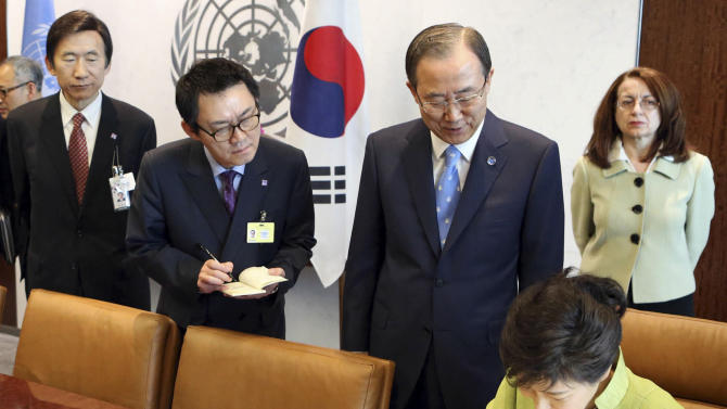"""In this May 6, 2013 photo, South Korean President's spokesman Yoon Chang-jung, third right top, watches South Korean President Park Geun-hye, right bottom, sign the guestbook as UN Secretary General Ban Ki-moon, second right, looks on, at United Nations headquarters. President Park's office says she has fired her chief spokesman Yoon after a """"disgraceful incident"""" during Park's trip to the United States. Media reports say the spokesman was accused of sexual abuse. (AP Photo/Yonhap, Do Kwang-hwan) KOREA OUT"""
