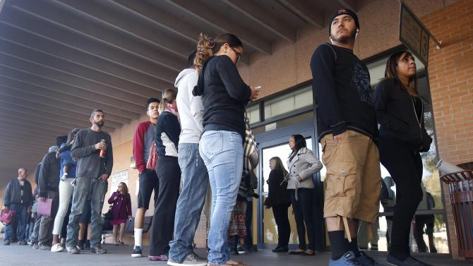 A line stretches outside an a Arizona Department of Transportation Motor Vehicle Division office, as many young immigrants protected from deportation under new Obama administration policies begin pursuing Arizona driver's licenses, Monday, Dec. 22, 2014, in Phoenix.  Monday marked the first day that about 20,000 immigrants in the country illegally who have received protection from deportation could apply for Arizona licenses. (AP Photo/Ross D. Franklin)