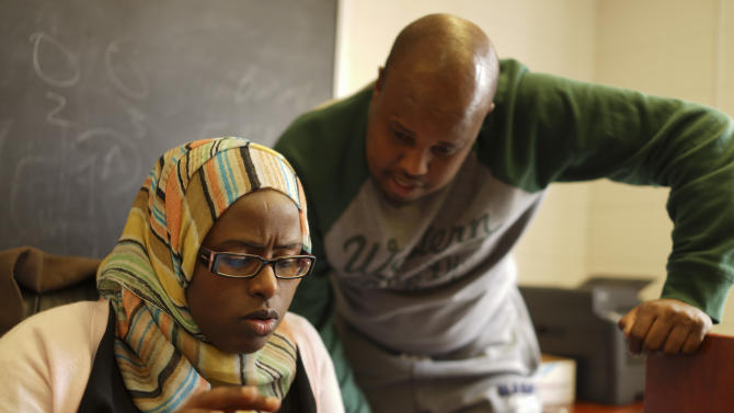 Hibo Guled, left, a navigator at Somali Health Solutions, checks data that Hassan Hared has stored on his phone while she helps him enroll in MNsure, Monday, March 31, 2014, in Minneapolis. The call center for Minnesota's online health insurance marketplace strained Monday under a crush of people trying to beat the midnight Monday deadline for open enrollment, while residents lined up to take advantage of locations offering in-person help. (AP Photo/Star Tribune, Jeff Wheeler)