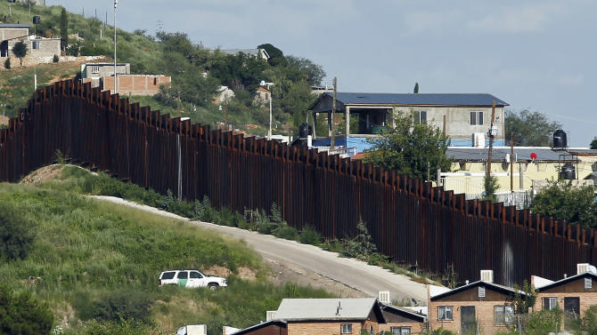 FILE - In this Aug. 9, 2012 file photo, a U.S. Border Patrol vehicle keeps watch along the border fence in Nogales, Ariz. A lawyer for the family of a teenage Mexican boy who was apparently fatally shot by a U.S. Border Patrol agent in October 2012, says an autopsy report shows the victim was struck by at least 11 bullets, mostly in his back. (AP Photo/Ross D. Franklin, File)