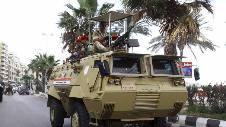 Soldiers on an army vehicle hold position outside a court in Alexandria