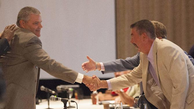 General Director of Labour Relations of General Motors David Wenner, left, shakes hands with chairperson of the CAW/GM Master Bargaining Committee Chris Buckley, right, as General Motors, Chrysler and Ford open contract talks with The Canadian Auto Workers union in Toronto Tuesday, Aug. 14, 2012. The Canadian Auto Workers union and the Detroit three automakers have started negotiations on new labor contracts amid charges that Canada is the most expensive place in the world to produce a vehicle. The CAW began negotiations with General Motors and Chrysler on Tuesday. They meet with Ford on Wednesday. (AP Photo/The Canadian Press, Michelle Siu)
