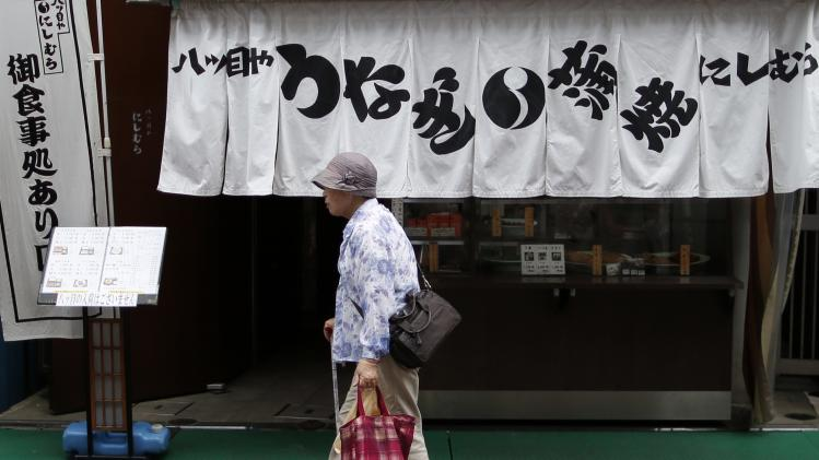 An elderly woman walks past an eel dish restaurant at Tokyo's Sugamo district, an area popular among the Japanese elderly, in Tokyo