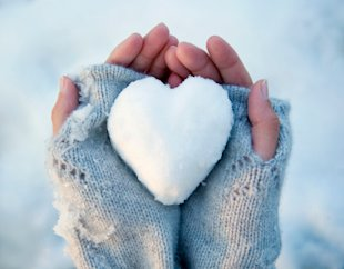 snow-shaped heart in handmittens winter