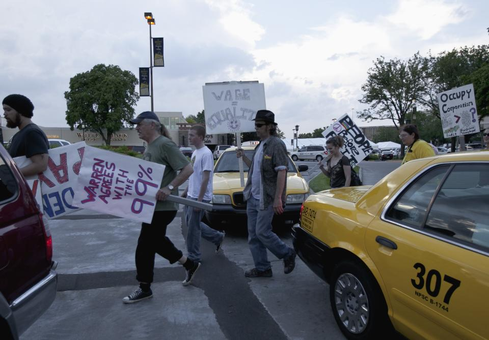 Members of Occupy Omaha picket outside the Berkshire-owned Borsheims jewelry store in Omaha, Neb., Friday, May 4, 2012, as a cocktail party for shareholders takes place. Berkshire Hathaway is expected to have 30,000 shareholders come to Omaha for it's annual shareholders meeting this weekend. (AP Photo/Nati Harnik)