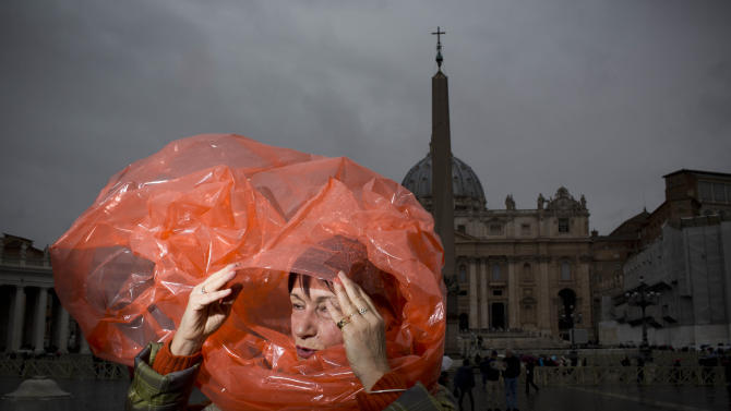 A woman takes cover from the rain in St. Peter's Square at the Vatican, Monday, March 18, 2013 the day ahead of the inaugural Mass of Pope Francis. The Vatican released details of the pope's installation Mass on Tuesday as well images of his coat of arms and fisherman's ring. In addition to more than 132 government delegations, the Vatican said 33 Christian delegations will be present, as well as representatives from Jewish, Muslim, Buddhist, Sikh and Jain communities. (AP Photo/Oded Balilty)